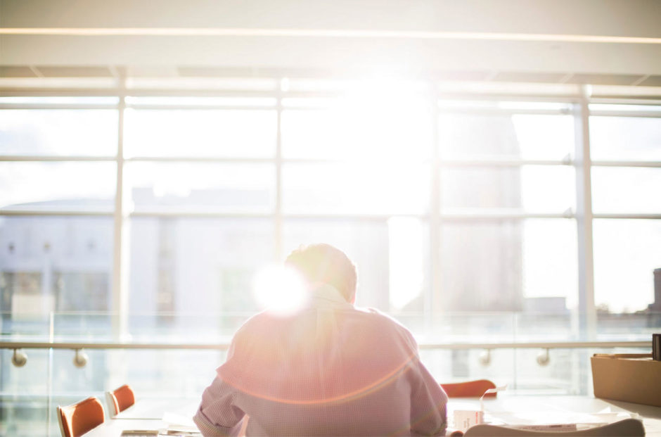 The-Ultimate-Guide-to-Hiring-Remote-Employees-man-at-desk-in-sunshine