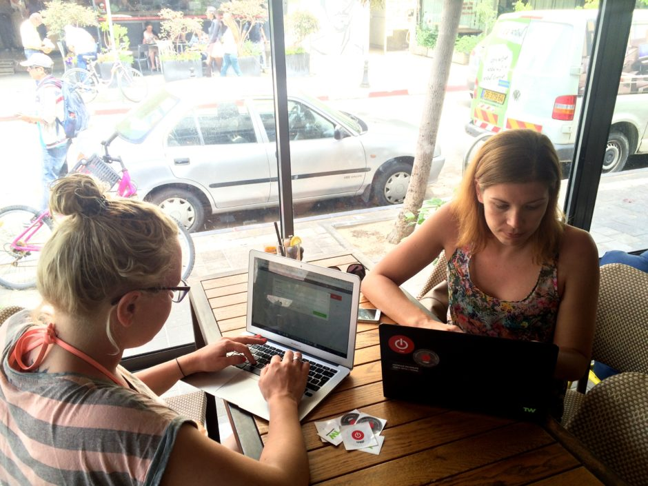 Two people working on their laptops in a cafe