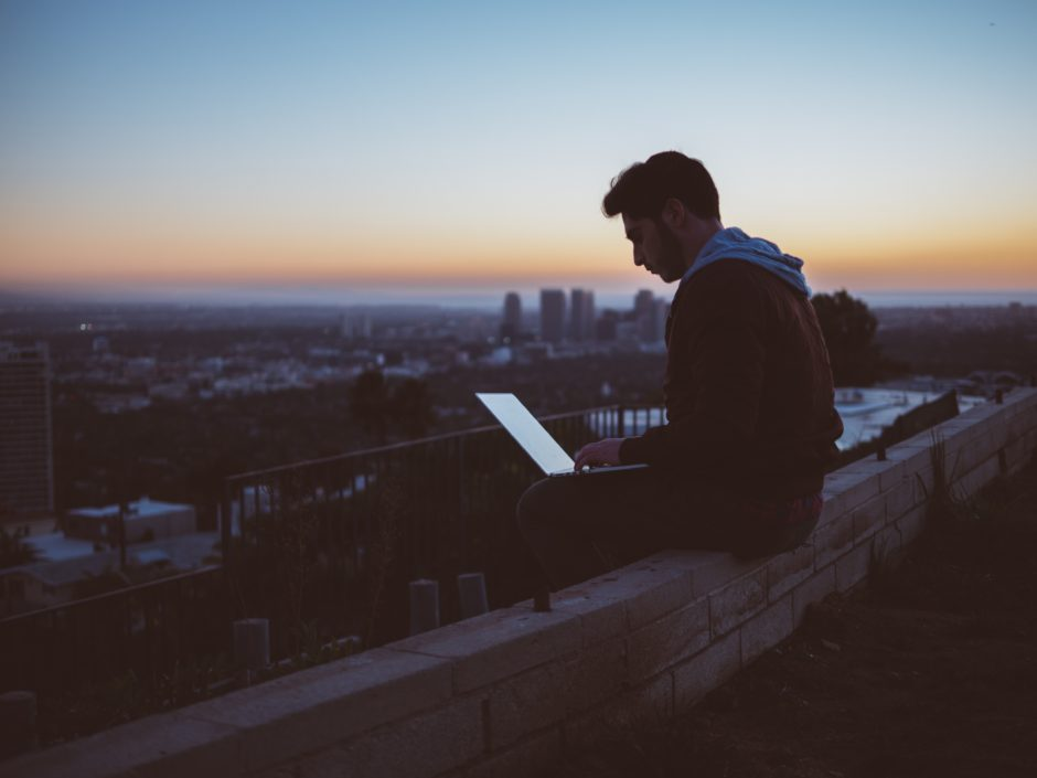 Man sitting on rooftop, looking at his tablet