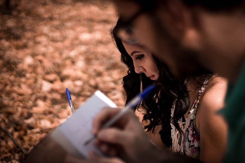 Two people writing in their notebooks