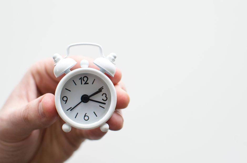 Hand carrying a mini clock