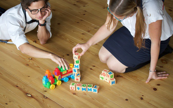 Two people playing with building blocks