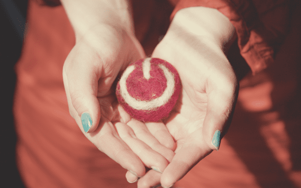Hands carrying a ball of yarn that is the Toggl logo