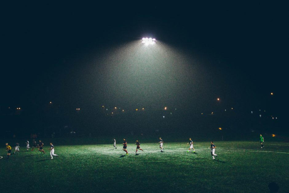 People playing football at night