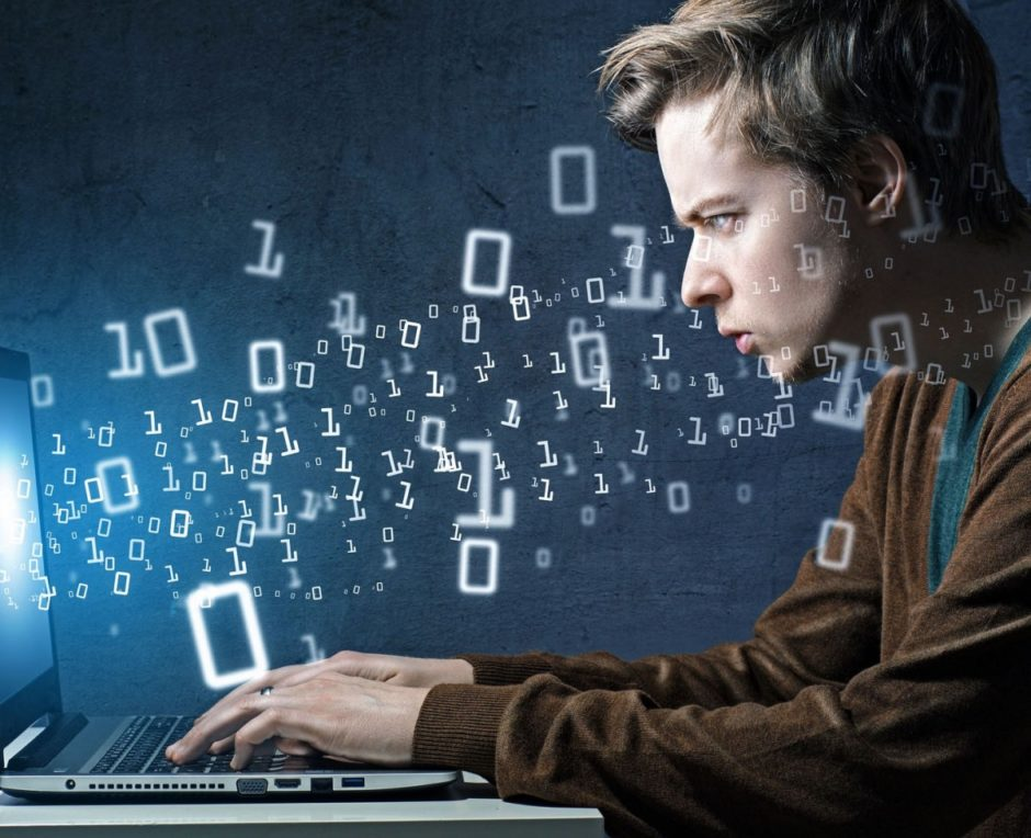 Man on his laptop with floating zeroes and ones around him