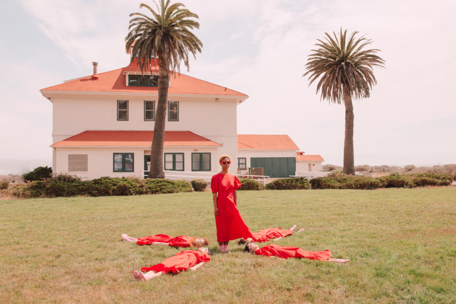 5 girls in matching red dresses put their hands in the air on a green field.