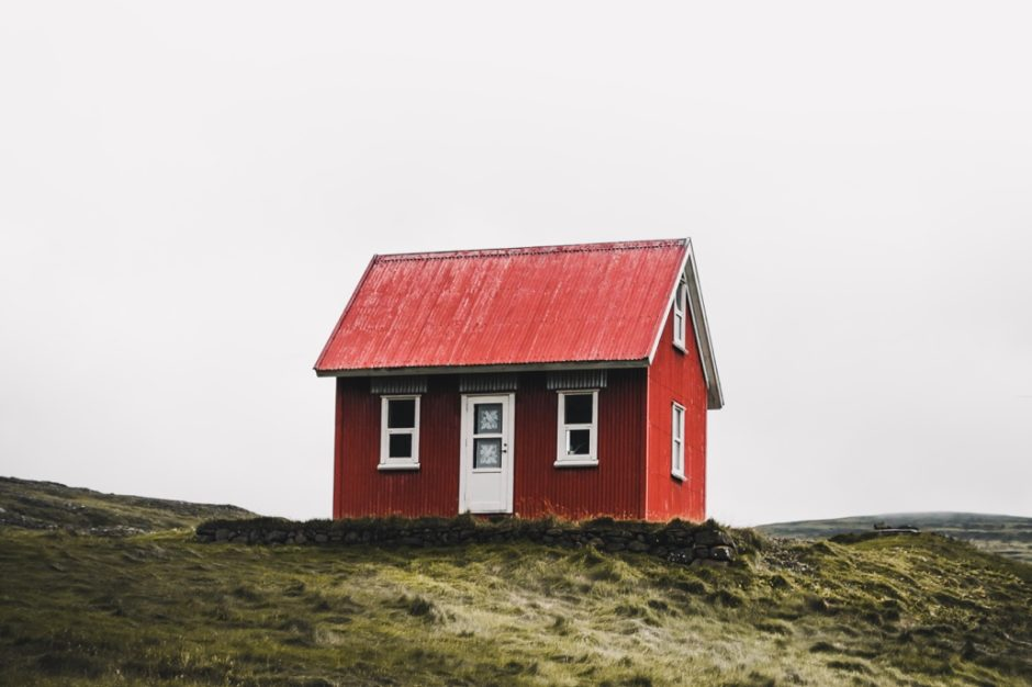 a red isolated house sitting on a hill